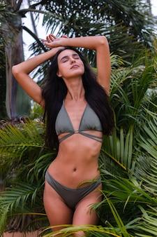 Porträt der gebräunten schlanken frau der passform im grünen winzigen bikini, der mit tropischen blättern aufwirft