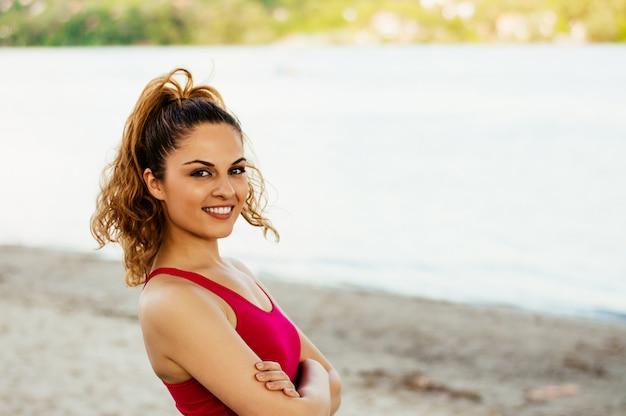 Porträt der geeigneten frau der junge im strand, der kamera betrachtet