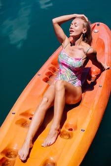 Porträt der geeigneten jungen kaukasischen touristenfrau im bikini, der auf kajak am schönen see in thailand entspannt. frau im urlaub, die sonnigen tag genießt.