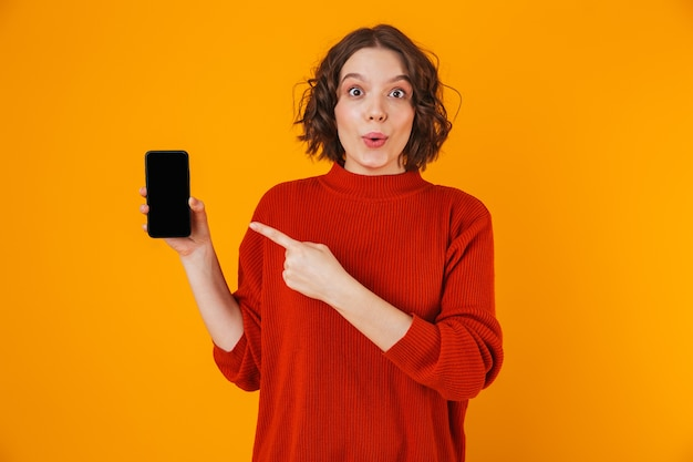 Porträt der gelockten frau 20s, die pullover hält und smartphone demonstriert, während sie lokal über gelb stehen