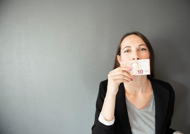 Porträt der geschäftsfrau, die 10 euro-scheine hält