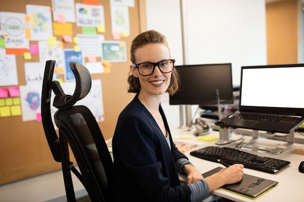 Porträt der geschäftsfrau, die am digitalisierer arbeitet