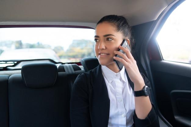 Porträt der geschäftsfrau, die am telefon auf dem weg zur arbeit in einem auto spricht. geschäftskonzept.