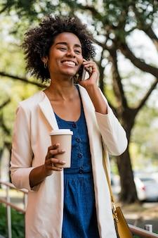 Porträt der geschäftsfrau, die am telefon spricht und eine tasse kaffee hält, während draußen im park steht. unternehmenskonzept.