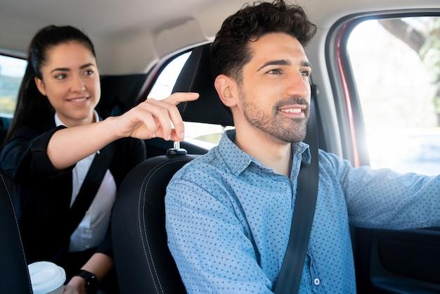 Porträt der geschäftsfrau, die etwas zu ihrem taxifahrer zeigt