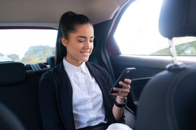 Porträt der geschäftsfrau, die ihr handy auf dem weg zur arbeit in einem auto benutzt. unternehmenskonzept.