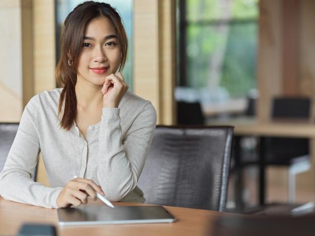Porträt der geschäftsfrau, die im arbeitsbereich mit tablette, stylus-stift und bürohintergrund lächelt