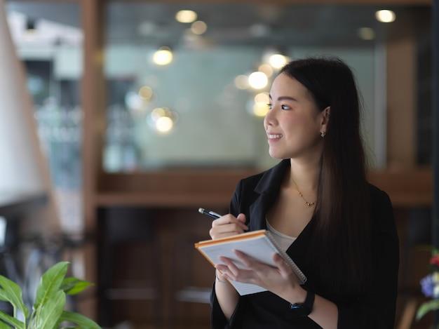 Porträt der geschäftsfrau, die mit zeitplanbuch arbeitet, während im besprechungsraum steht