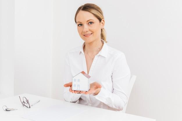 Porträt der geschäftsfrau miniaturhausmodell im büro halten