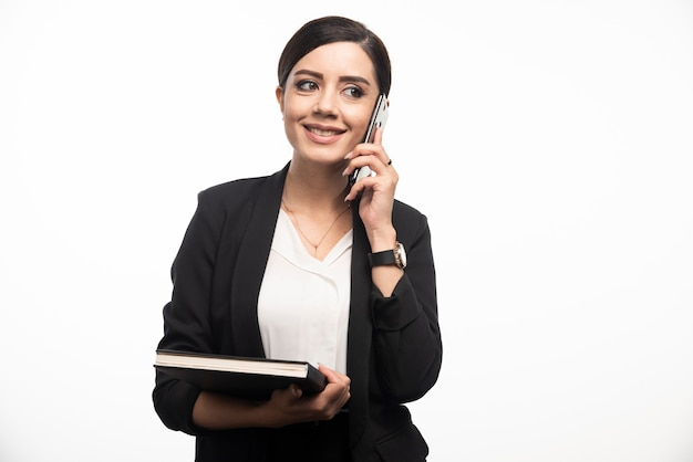 Porträt der geschäftsfrau mit dem notizbuch, das am telefon spricht.