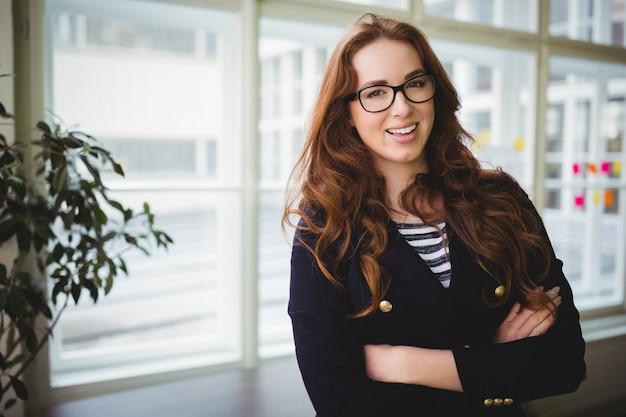 Porträt der geschäftsfrau mit den armen kreuzte im kreativen büro