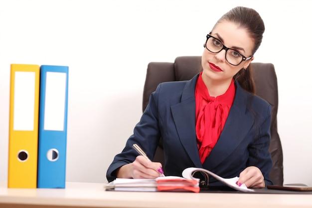 Porträt der geschäftsfrau mit laptop schreibt auf ein dokument in ihrem büro