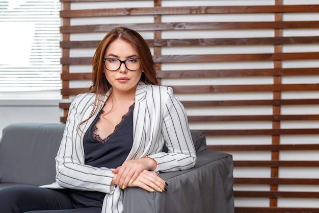 Porträt der geschäftsfrau sitzend auf sofa in modern office
