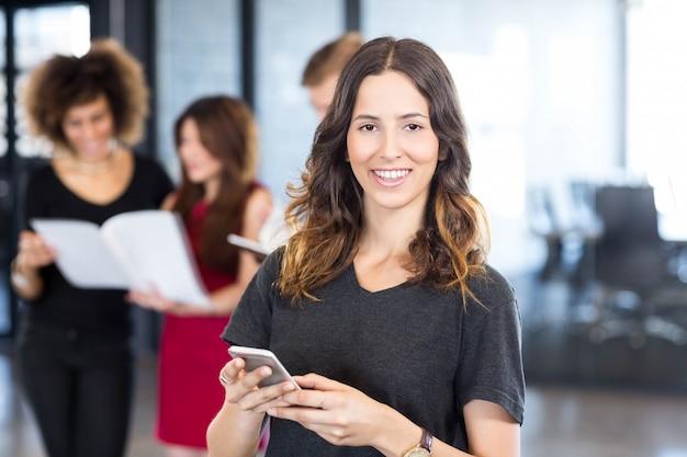 Porträt der geschäftsfrau-versenden von sms-nachrichten auf smartphone während ihre kollegen, die hinter ihr im büro stehen