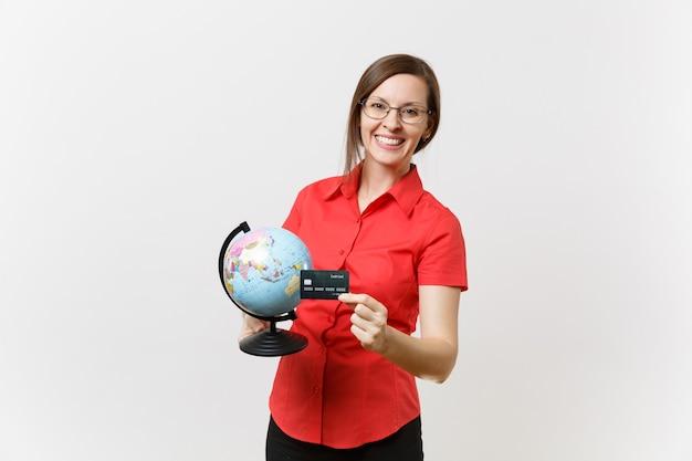 Porträt der geschäftslehrerfrau in den roten hemdrockgläsern, die kugel und kreditkarte lokalisiert auf weißem hintergrund halten. bildungslehre an der high school universität, tourismus, auslandsstudium konzept.