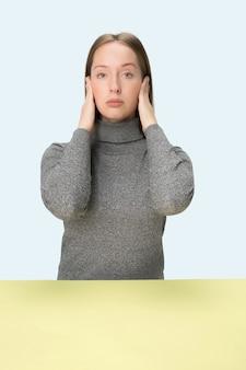 Porträt der gestressten frau, die mit geschlossenen augen sitzt und mit händen bedeckt. isoliert auf blauem studiohintergrund.