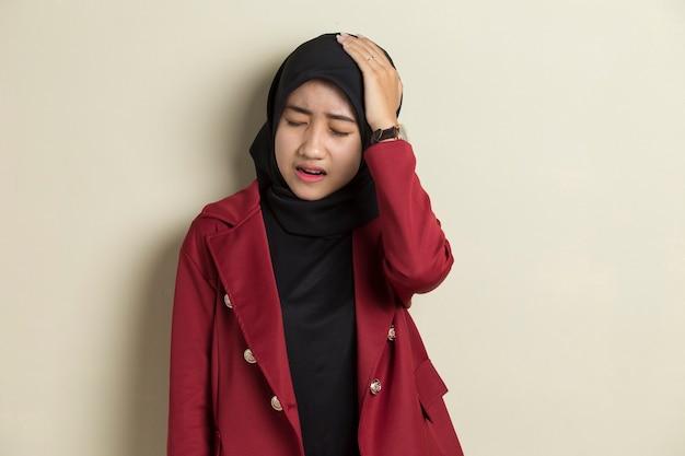 Porträt der gestressten kranken muslimischen frau mit kopfschmerzen kranke frau leidet unter schwindel, schwindel, migräne, kater, gesundheitskonzept junge erwachsene asiatische frau modell