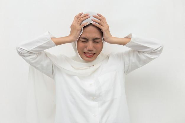 Porträt der gestressten kranken muslimischen frau mit kopfschmerzen kranke frau leidet unter schwindelschwindel migräne-kater-gesundheitskonzept junge erwachsene asiatische frau modell