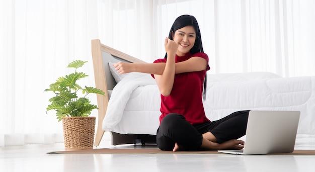 Porträt der gesunden jungen asiatischen frau, die yogaübungen praktiziert, die im schlafzimmer sitzen und online auf laptop zu hause lernen.