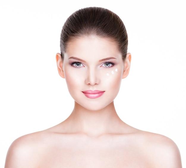 Porträt der gesunden schönen frau mit kosmetischer creme unter den augen - lokalisiert auf weiß.