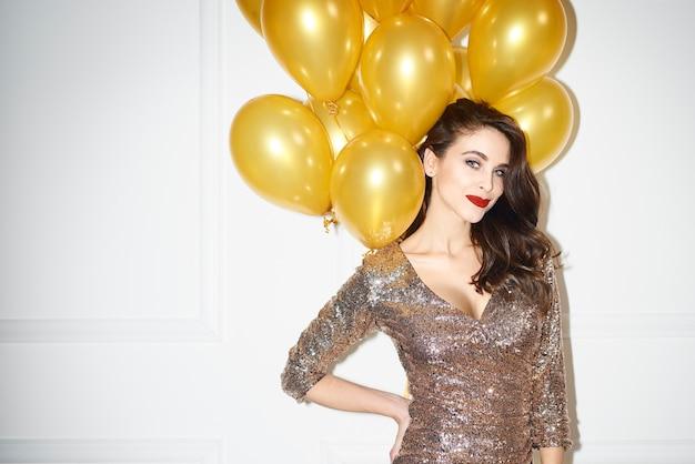 Porträt der glamourösen frau mit goldenen luftballons
