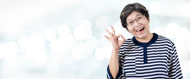 Porträt der glücklichen älteren asiatischen frauengeste oder des zeigens von hand okay