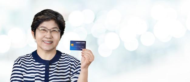 Porträt der glücklichen älteren asiatischen frauengriffkreditkarte