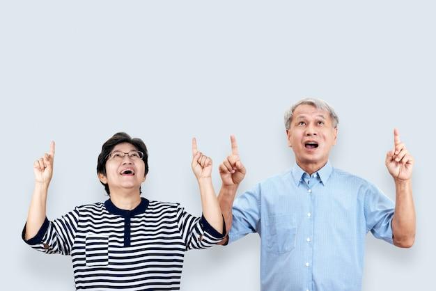 Porträt der glücklichen älteren asiatischen paargeste oder hand und finger oben zeigen
