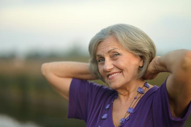 Porträt der glücklichen älteren frau, die draußen aufwirft