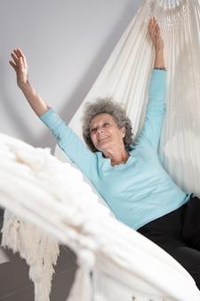 Porträt der glücklichen älteren frau, die in der hängematte und im ausdehnen liegt