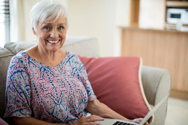 Porträt der glücklichen älteren frau, die laptop im wohnzimmer zu hause verwendet