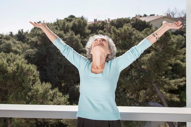 Porträt der glücklichen älteren frau, die mit den angehobenen armen steht