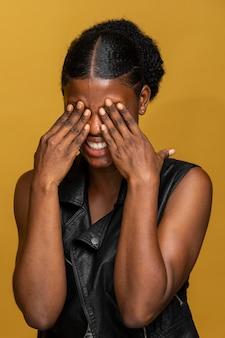 Porträt der glücklichen afrikanischen frau, die ihre augen bedeckt