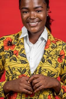 Porträt der glücklichen afrikanischen frau im blumenmantel