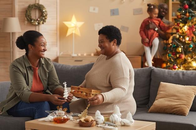 Porträt der glücklichen afroamerikanischen familie, die haus für weihnachten mit mutter und tochter im vordergrund, kopierraum verziert