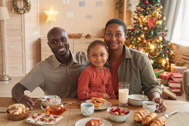 Porträt der glücklichen afroamerikanischen familie, die tee und süßigkeiten genießt, während weihnachten zu hause im gemütlichen innenraum feiert