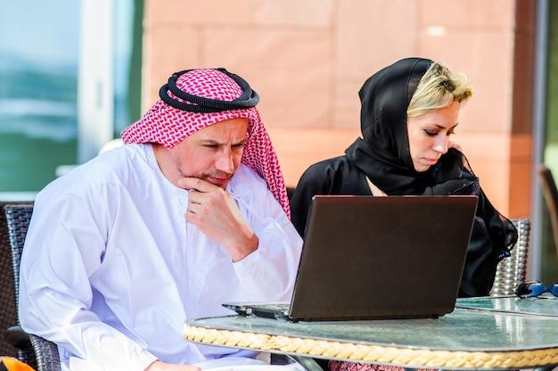 Porträt der glücklichen arabischen geschäftsfrau und des geschäftsmanns im tropischen sommercafé. freiberufliche und fernarbeit. verliebte arabische frau und arabisches mannpaar arbeiten zusammen am ufer