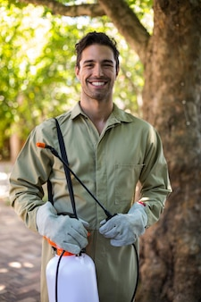 Porträt der glücklichen arbeitskraft mit insektizidsprüher