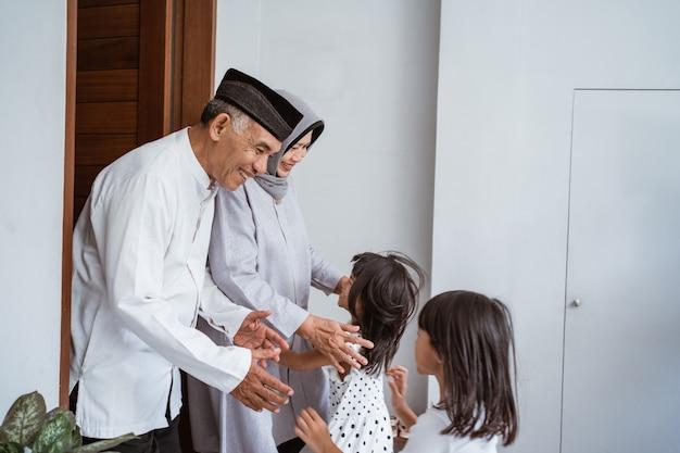 Porträt der glücklichen asiatischen muslimischen familie, die großeltern auf ramadan kareem besucht. indonesische leute, die eid mubarak feiern