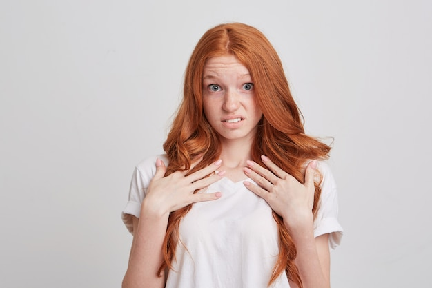 Porträt der glücklichen aufgeregten rothaarigen jungen frau mit langen haaren