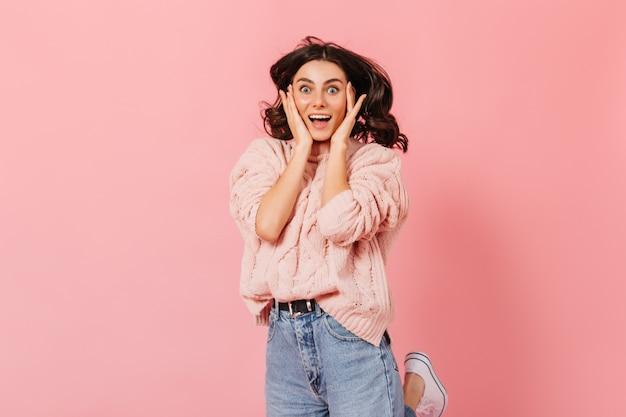 Porträt der glücklichen blauäugigen dame im rosa pullover. gelockte brünette frau schaut glücklich in kamera auf lokalisiertem hintergrund.