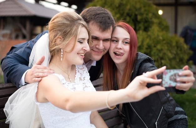 Porträt der glücklichen braut und des bräutigams, die am hochzeitstag selfie mit dem gast machen