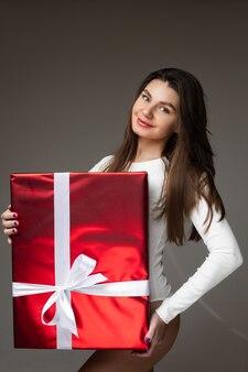Porträt der glücklichen brünetten frau, die rote geschenkbox hält und kamera betrachtet, lokalisiert auf grauer wand