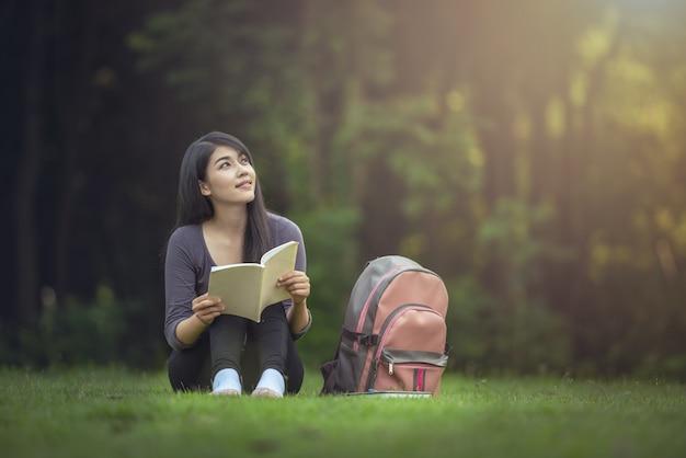 Porträt der glücklichen charmanten asiatischen frau, die ein buch im freien liest