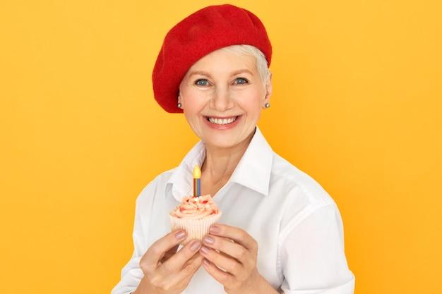 Porträt der glücklichen charmanten kaukasischen frau mittleren alters in der stilvollen roten kopfbedeckung, die ihren geburtstag feiert, lokalisiert mit cupcake in ihren händen. konzept für feier, party und besondere anlässe