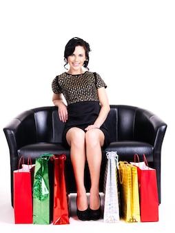 Porträt der glücklichen eleganten frau im schwarzen kleid mit einkaufstüten, die auf der couch lokalisiert auf weißer wand sitzen.