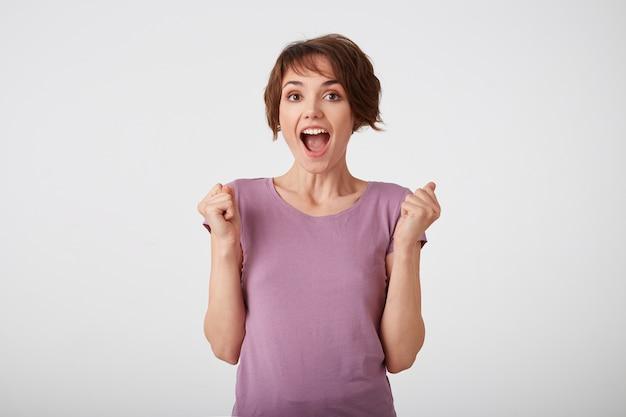Porträt der glücklichen erstaunten fröhlichen kurzhaarigen dame im leeren t-shirt, hörte erstaunte nachrichten, steht über weißem hintergrund mit weit geöffneten augen und mund.