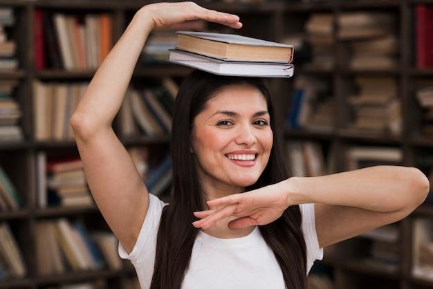 Porträt der glücklichen erwachsenen frau an der bibliothek