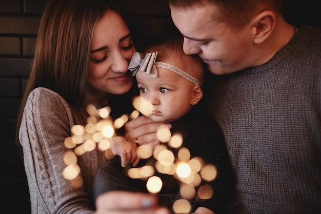 Porträt der glücklichen familie, der mutter, des vatis und des babys mit wunderkerzen in der front,