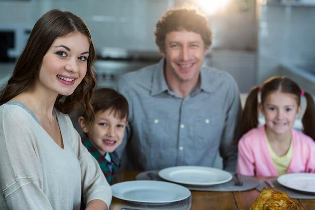 Porträt der glücklichen familie, die auf einem esstisch sitzt